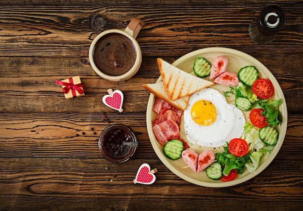 Café da manhã no dia dos namorados - ovo frito em forma de coração, torradas, salsicha, bacon e legumes frescos. café da manhã inglês. xícara de café. vista do topo Foto gratuita