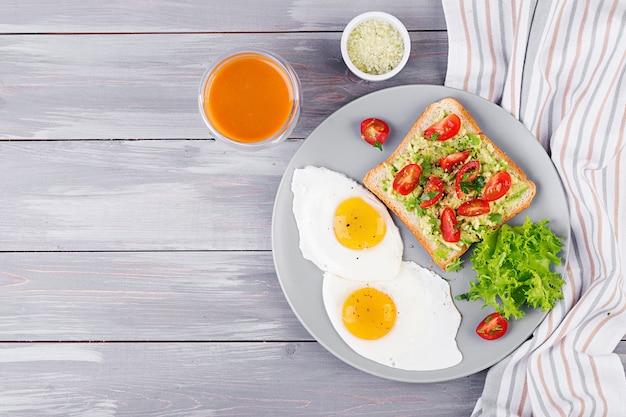 Café da manhã. ovo frito, salada vegetal e um sanduíche grelhado do abacate em um fundo cinzento. vista do topo Foto Premium