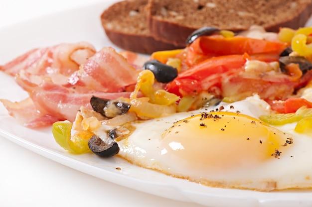 Café da manhã - ovos fritos com bacon, tomate, azeitona e fatias de queijo Foto gratuita
