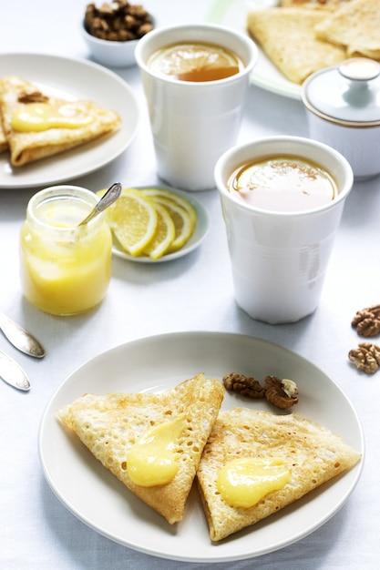 Café da manhã para dois com panquecas, creme de limão e chá. café da manhã no dia dos namorados. Foto Premium