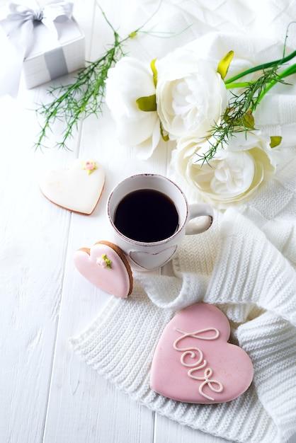 Café da manhã romântico na cama. café, biscoitos, caixa de presente e flor na mesa de madeira. conceito de dia dos namorados Foto Premium