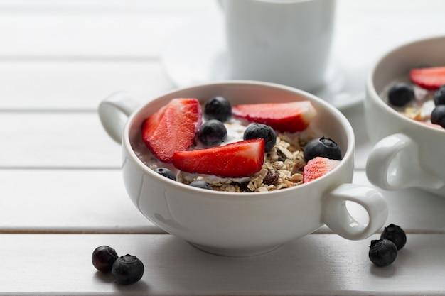 Café da manhã saboroso com farinha de aveia, iogurte, morango, mirtilo, mel e leite em fundo de madeira branco com espaço de cópia. fechar-se. Foto gratuita