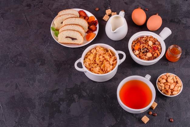 Café da manhã saboroso e útil com flocos, leite, nozes e frutas secas Foto Premium