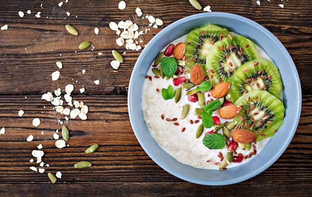 Café da manhã saudável. aveia com kiwi, romã, sementes de linho e nozes. menu de desintoxicação. vi superior Foto Premium