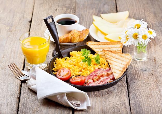 Café da manhã saudável com ovos mexidos, suco e frutas na mesa de madeira Foto Premium