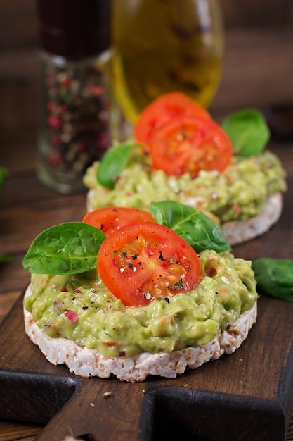 Café da manhã saudável. sanduíche de pão torrado com guacamole e tomate em uma mesa de madeira. Foto gratuita