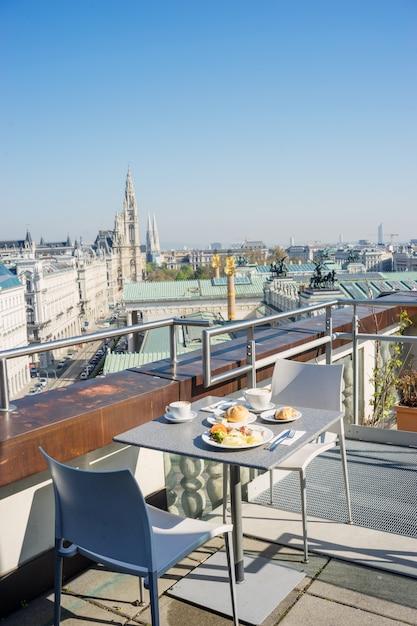 Café da manhã servido em um telhado do edifício da cidade europeia Foto Premium