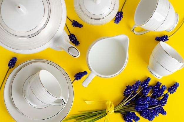 Café de porcelana branca ou jogo de chá com flores de muscari em amarelo Foto Premium