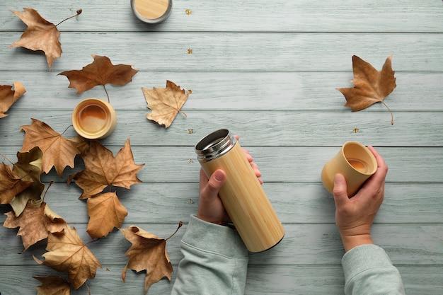 Café de zero desperdício em xícaras de bambu de frasco de metal isolado ecologicamente correto no outono. mãos segurando o frasco e a xícara. Foto Premium