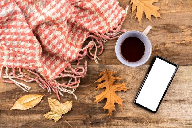 Café e cachecol em fundo de madeira Foto gratuita