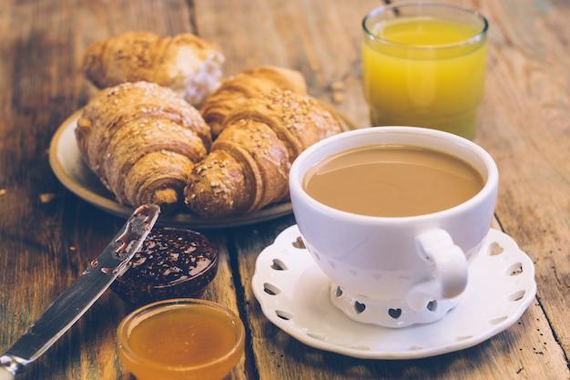 Café e croissants com geléia e suco de laranja. café da manhã típico francês (petit déjeuner) Foto Premium