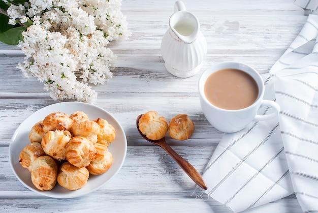 Café e éclairs em uma mesa branca Foto Premium