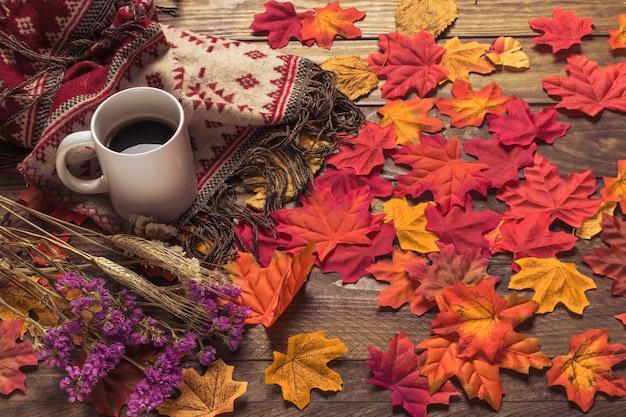 Café e manta perto de folhas e flores Foto gratuita