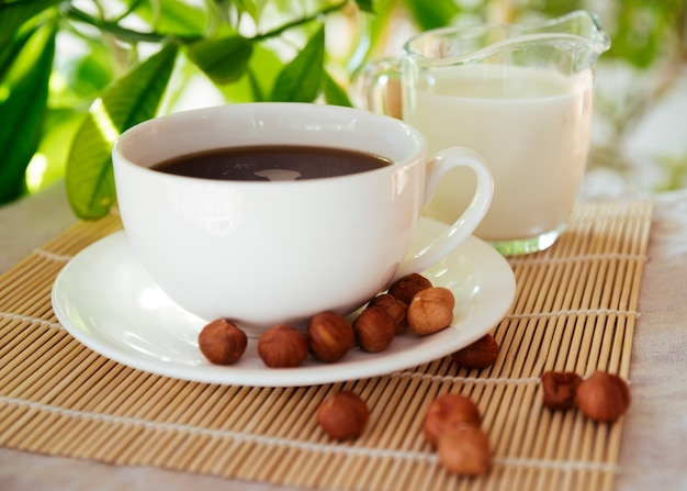 Café e nozes na esteira de bambu Foto gratuita