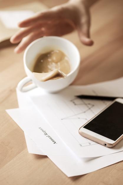 Café em copo branco, derramando sobre a mesa de manhã na mesa do escritório Foto gratuita