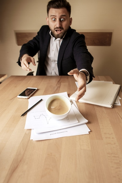 Café em copo branco, derramando sobre a mesa no dia útil da manhã na mesa de escritório Foto gratuita