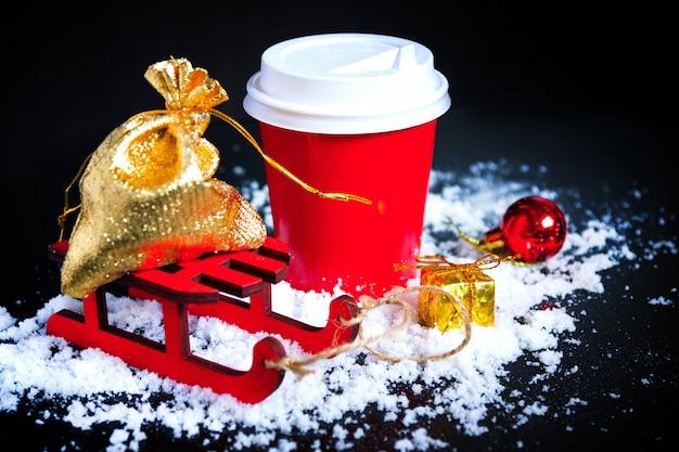 Café em copo vermelho com presente de natal em fundo preto Foto Premium