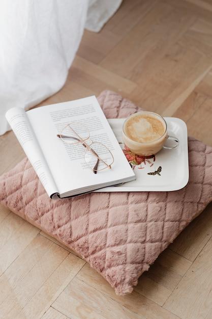 Café em uma almofada de veludo rosa com uma revista aberta Foto gratuita