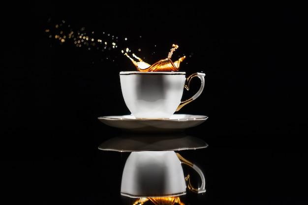Café espirra no copo branco no fundo preto Foto gratuita
