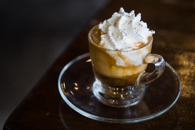 Café expresso com creme de leite fresco na mesa de madeira Foto Premium