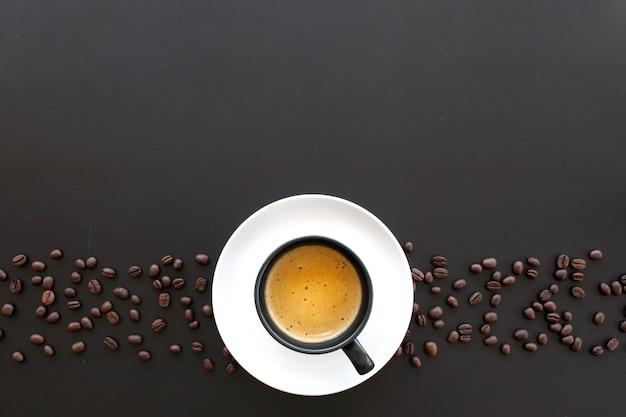 Café expresso e café em grão na mesa preta Foto Premium