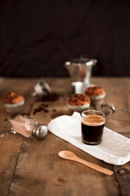Café expresso, em, vidro, branco, guardanapo, com, cacau, shaker, e, colher madeira Foto gratuita