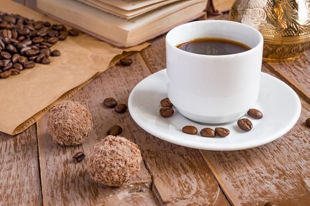 Café fresco abreviado em bebida de manhã cezve em copo branco ao lado de bolas de chocolate Foto Premium