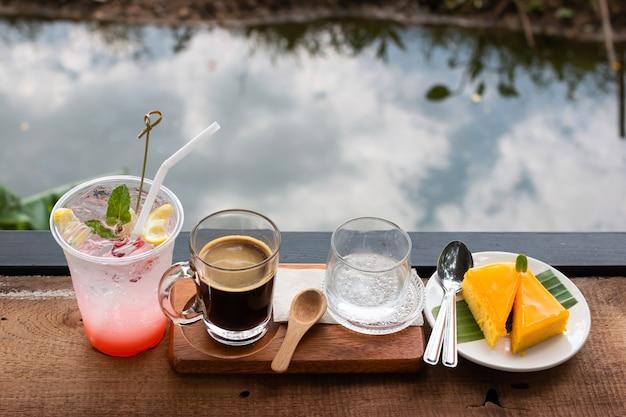 Café fresco em um copo e suco de lichia e bolo de laranja misturado com limão Foto Premium