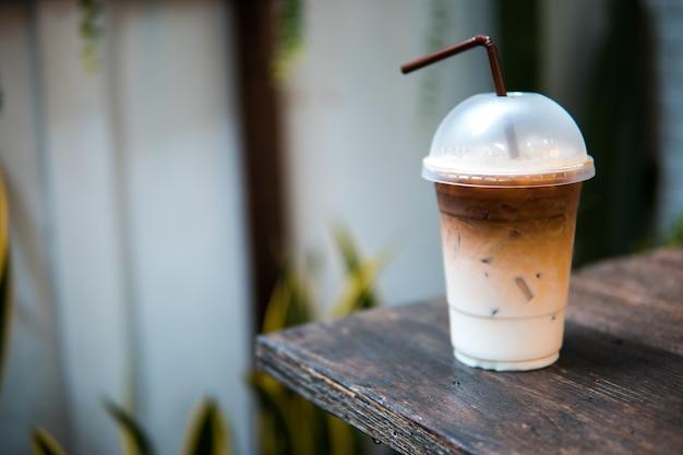 Café gelado com canudo na mesa de madeira Foto Premium