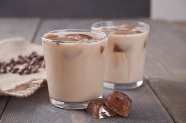 Café gelado do latte com cubos de gelo e feijões de café em uma tabela. Foto Premium