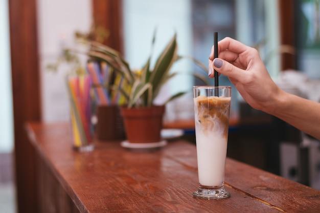 Café gelado em um copo alto com creme derramado Foto Premium