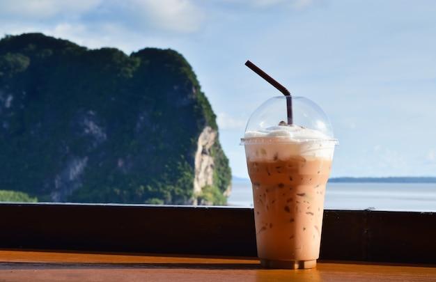 Café gelado em um copo de plástico contra o mar Foto Premium