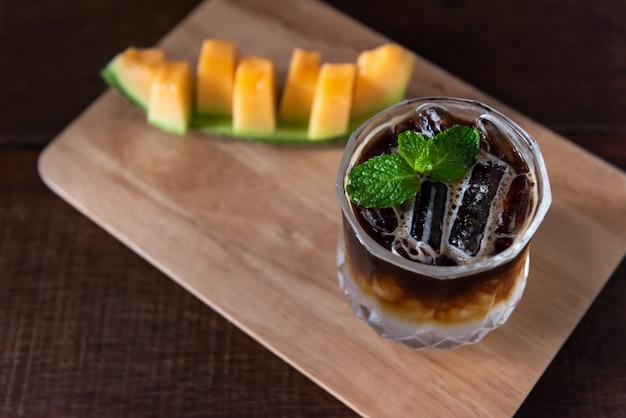 Café gelado em vidro com melão na placa de madeira Foto Premium