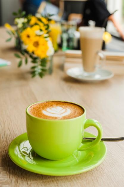 Café latte saboroso com latte art em copo verde no restaurante Foto gratuita