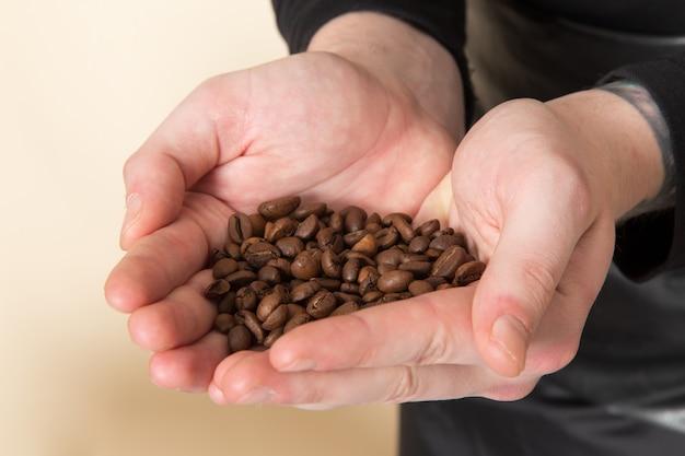 Café marrom sementes baristna segurando nas mãos Foto gratuita
