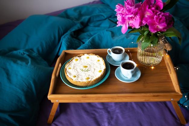 Café, peônias rosa, cheesecake em uma bandeja de madeira Foto Premium