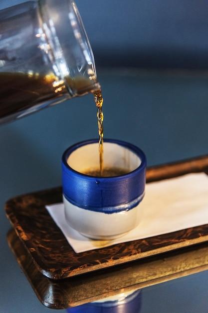 Café preto em um pequeno copo azul Foto gratuita