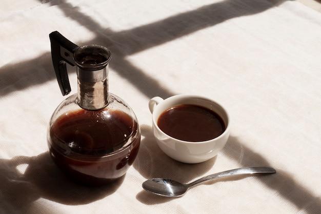 Café preto em xícara com colher de chá Foto gratuita