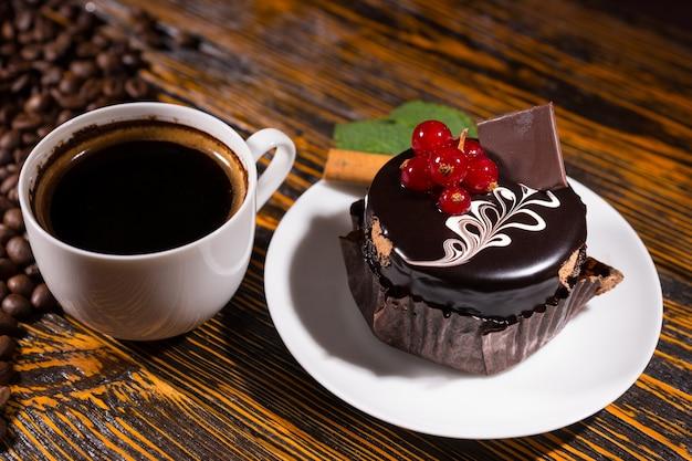 Café preto fresco em caneca de bolinho de chocolate Foto Premium