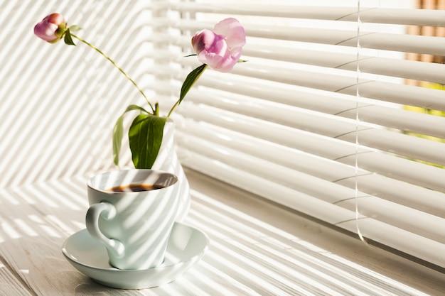 Café preto quente e vaso de flores no peitoril da janela Foto gratuita