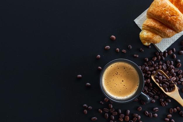 Café quente, croissants de feijão e manteiga na mesa preta Foto Premium