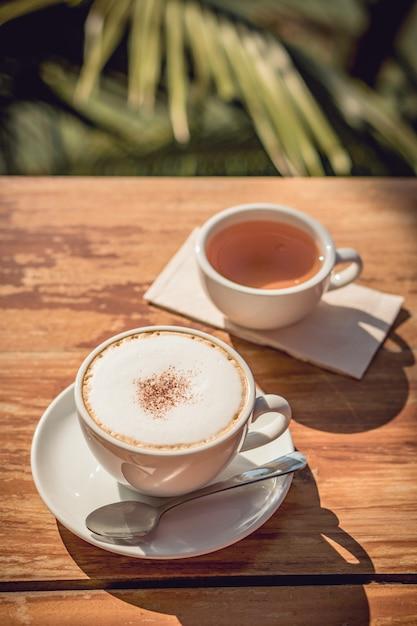 Café quente e lugar de chá quente na mesa de madeira no início da manhã com copyspace Foto Premium