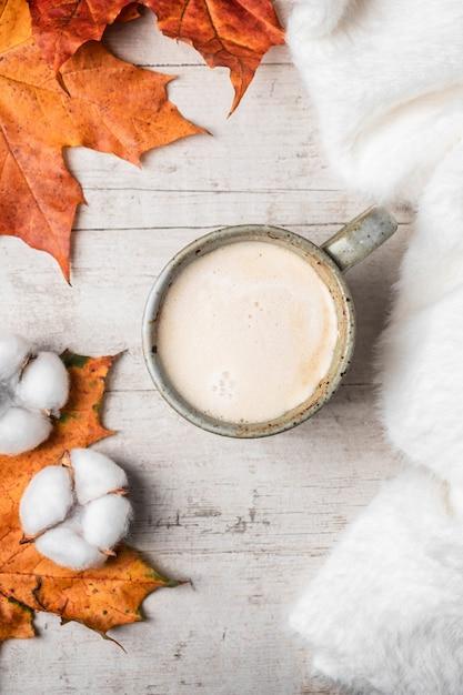 Café, suéter fofo branco sobre um fundo branco e folhas de outono maple. Foto Premium