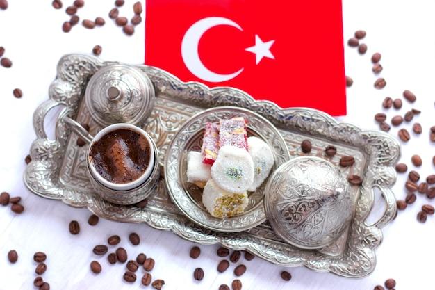 Café turco em uma bandeja de prata tradicional com doces turcos e a bandeira vermelha da turquia Foto Premium