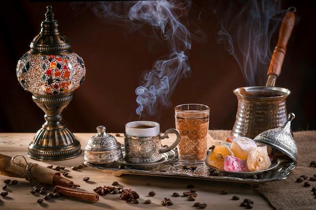 Café turco no cezve e no prazer turco tradicional. vapor sobre um copo. lâmpada antiga Foto Premium
