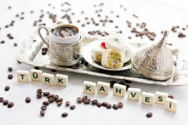 Café turco tradicional e doces na pratas. lettering - café turco - em língua turca Foto Premium