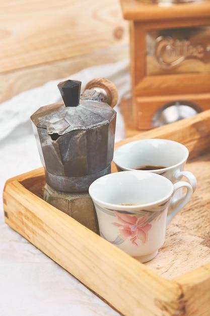 Cafeteira com duas xícaras de café na bandeja de madeira Foto Premium