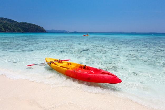 Caiaques coloridos na praia da ilha tropical, tailândia Foto Premium