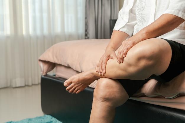 Cãibra nas pernas, mulher idosa sofrendo de cãibras nas pernas em casa, conceito de problema de saúde Foto Premium