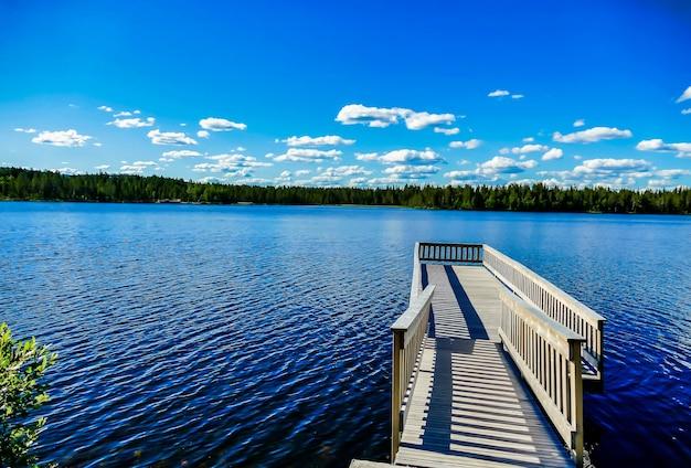 Cais de madeira sobre o belo lago com as árvores e o céu azul ao fundo na suécia Foto gratuita